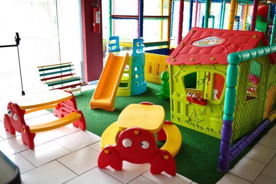 Área baby com escorregador, casinha de boneca, gangorras, mini piscina de bolinhas e mesinhas